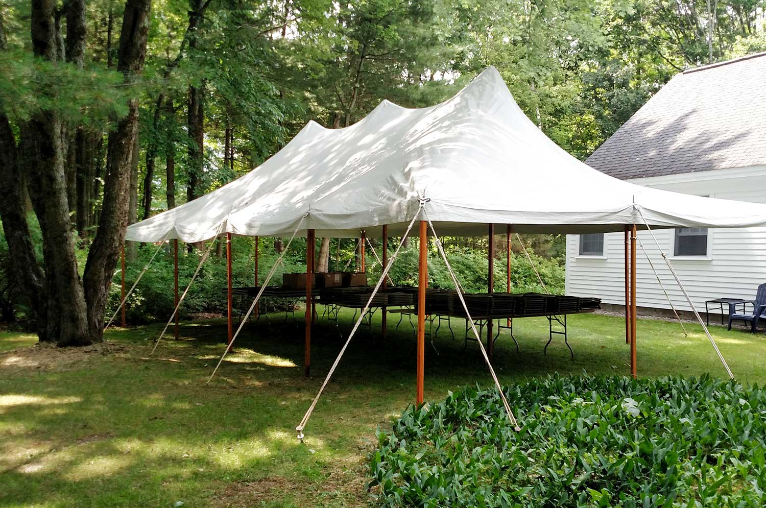 White tent with cedar poles set up in beautifully landscaped yard